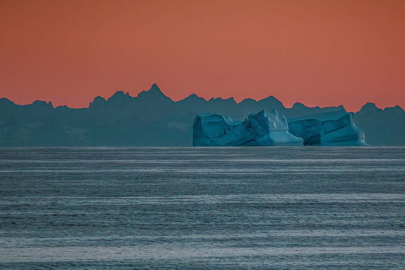 23:56h – Mitternachtssonne, riesige Eisberge vor einer schroffen Küstenlinie, NO von Kulusuk, Ostgrönland